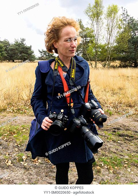Regte Heide, Riel, Netherlands. Female redheaded photographer wearing three, heavy dslr cameras wile taking a stroll through a forest on a Saturday afternoon
