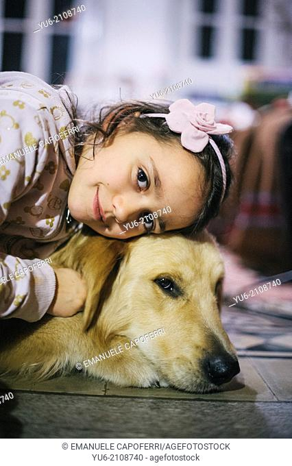 Little girl and her dog golden retriever, rests his head on the dog