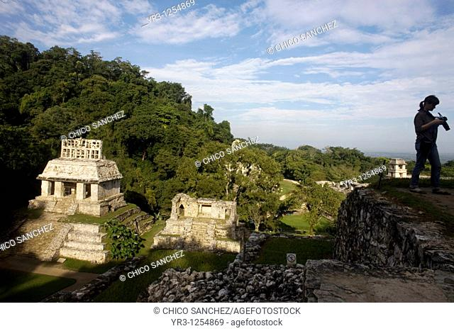 A tourist looks at her camera as the sun illuminates the Temple of the Sun in the ancient Mayan city of Palenque, Chiapas, Mexico