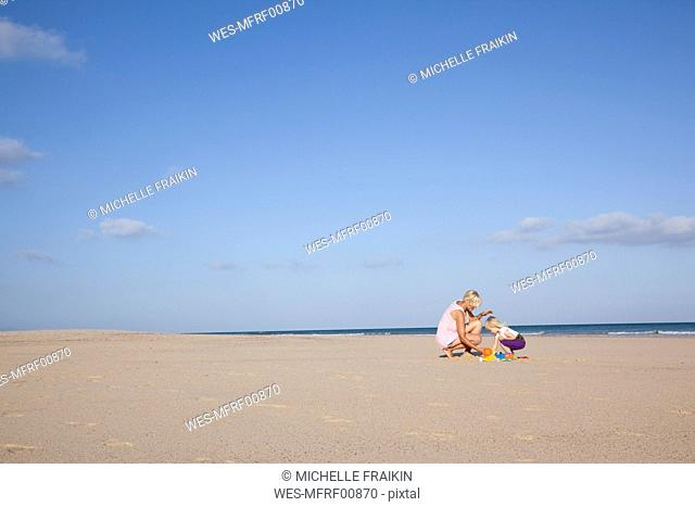 Spain, Fuerteventura, mother and daughter playing on the beach