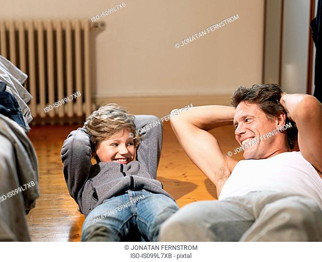Mature man and son performing exercises in bedroom