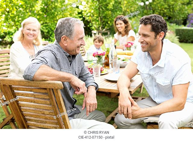 Family sitting at table outdoors
