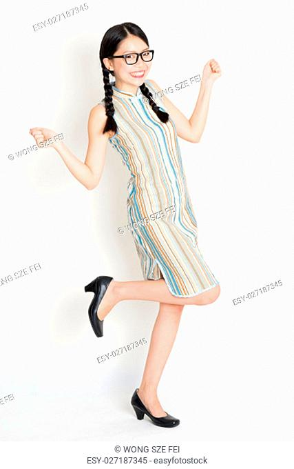 Portrait of excited young Asian girl in traditional qipao dress jumping around and hand holding something, full length standing on plain background
