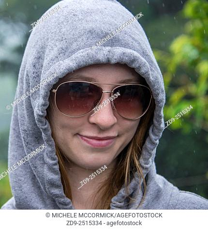 A pretty young woman is hooded in the rain