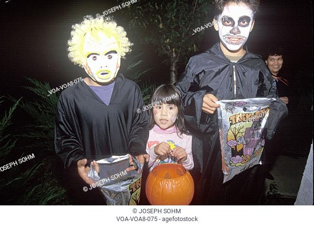 Three children trick or treating for Halloween in Oak View, CA