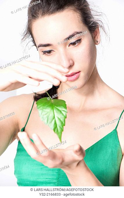 Woman looking amazed at green leaf floating in the air. Conceptual image of environment and the wonder of nature