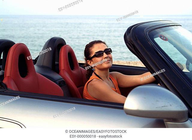Woman in car by beach