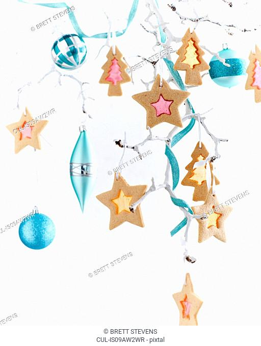 Star shaped stained glass biscuits and baubles hanging from painted white branch