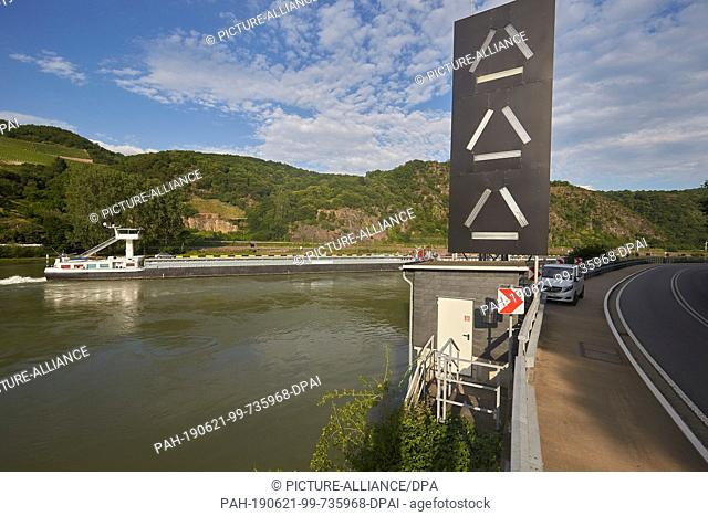 19 June 2019, Rhineland-Palatinate, St. Goar: A cargo ship passes the traffic lights at Betteck opposite the Loreley rock on the Middle Rhine