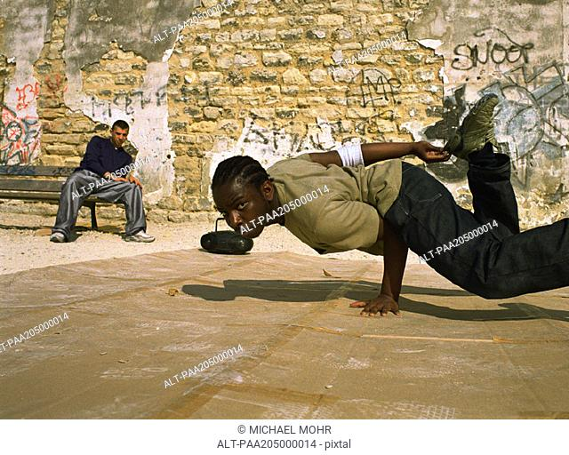Man balancing on hand, break dancing, man in background sitting on bench