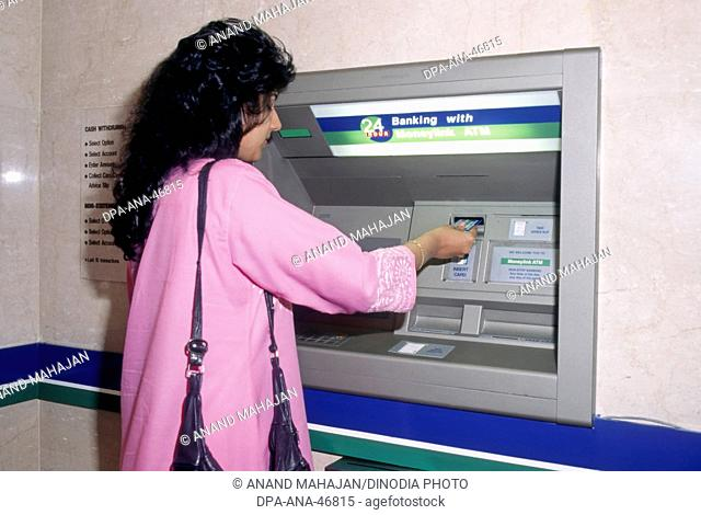 woman operating Any Time Money System ATM , automated bank system