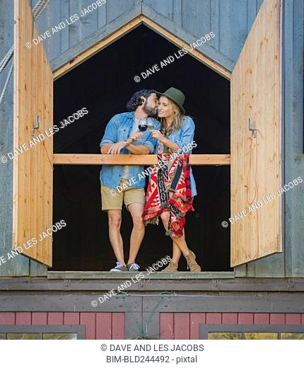Hispanic couple standing near open barn doors drinking wine