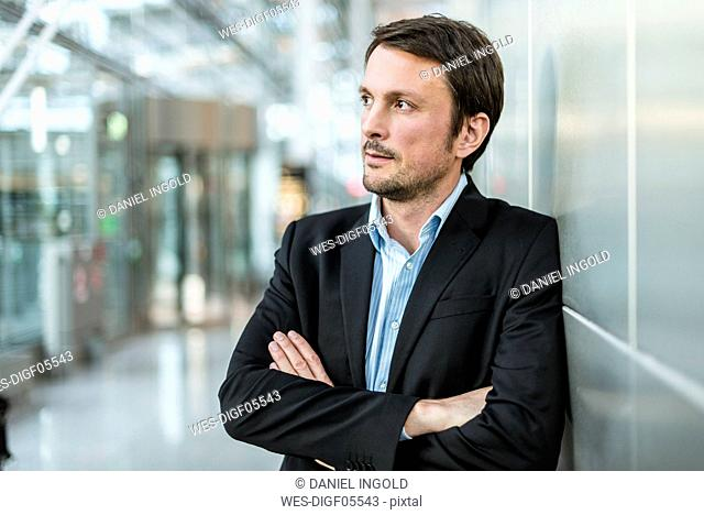 Businessman waiting at the airport with arms crossed