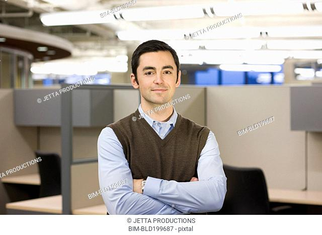 Caucasian businessman standing in cubicle with arms crossed