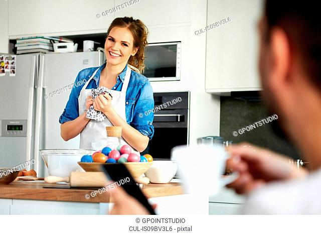 Couple talking and baking in kitchen