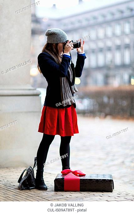 Mature woman with Christmas gift taking photographs of city, Copenhagen, Denmark