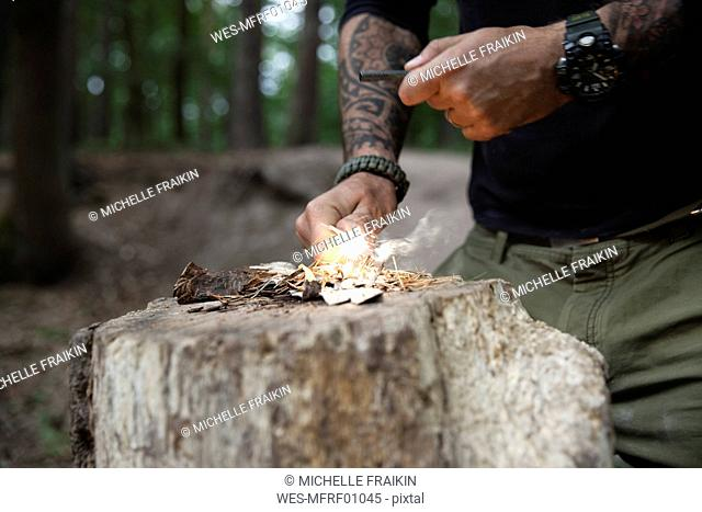 Man igniting a fire on tree stump in the forest