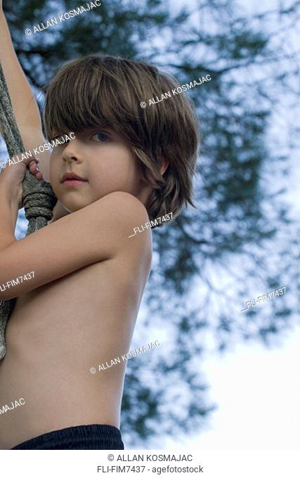 Portrait of a young boy on a rope swing, Muskoka, Ontario