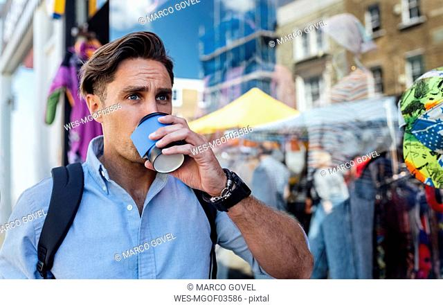UK, London, Portobello Road, portrait of man drinking coffee in front of a shop window