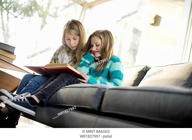 Two girls sitting on a sofa, reading a book