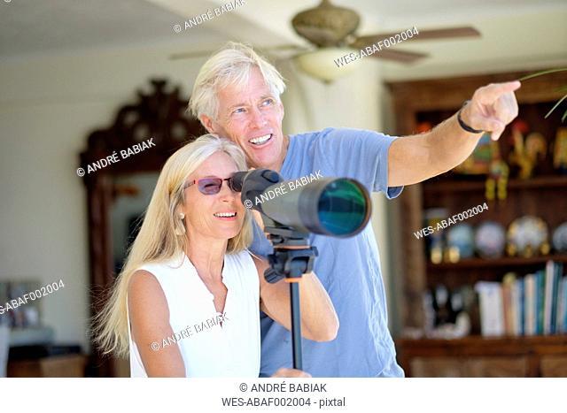 Senior couple looking through telescope