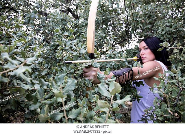 Archeress aiming with a bow in a forest