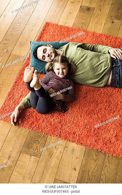 Father and daughter lying on carpet on the floor