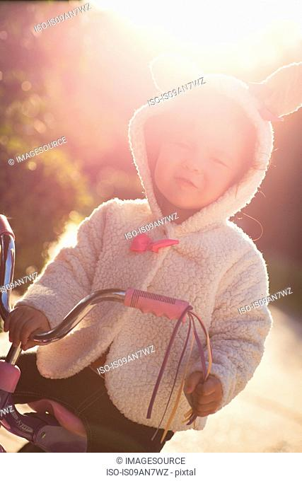 Little girl learning to ride tricycle