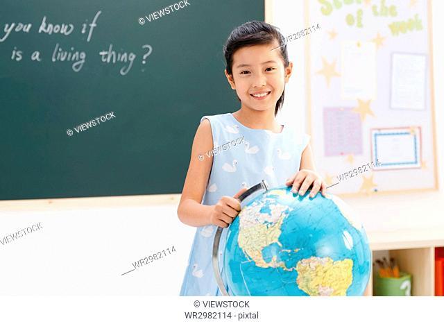 Portrait of school girl with globe