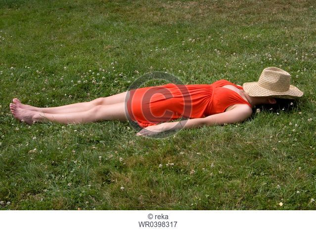 Young woman lying in meadow with straw hat covering her face