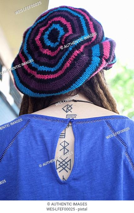 Rear view of young woman with dreadlocks wearing wooly hat