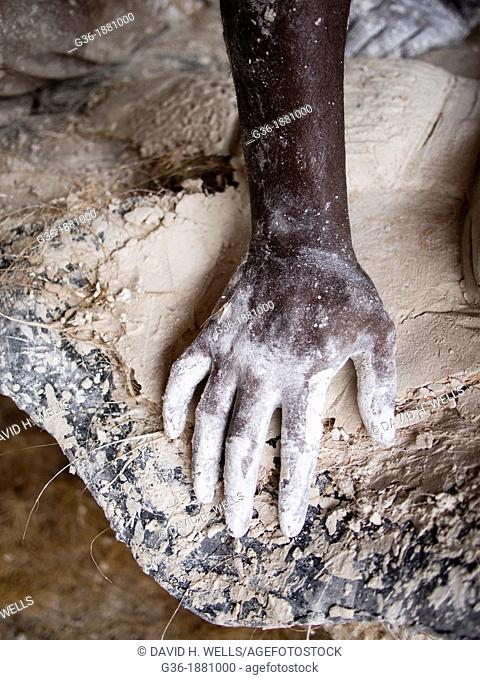 A worker's hand covered with plaster in Ahmedabad, India