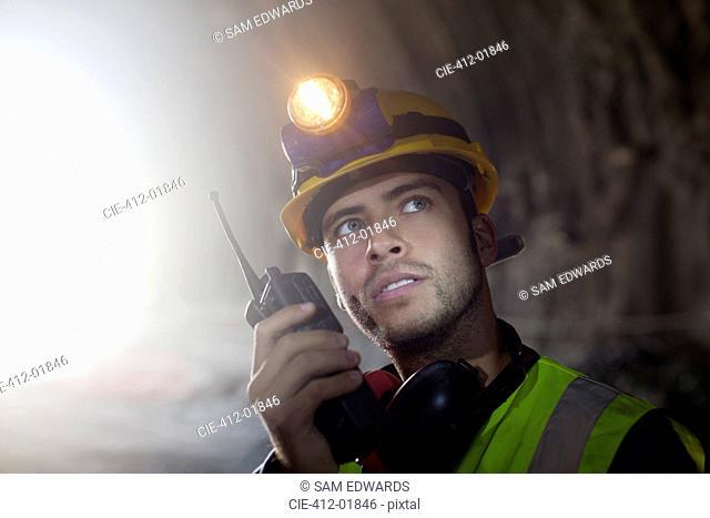 Worker using walkie-talkie in tunnel