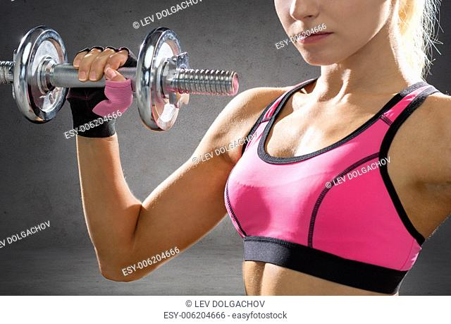 fitness, sport, exercising and people concept - close up of sporty woman with heavy steel dumbbells over concrete wall background