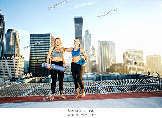 Women holding yoga mats on urban rooftop