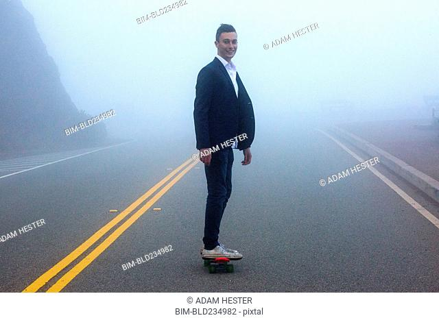 Caucasian man standing on small red skateboard in fog