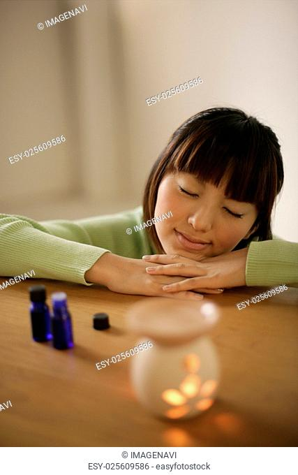 Woman lying beside an aromatherapy burner
