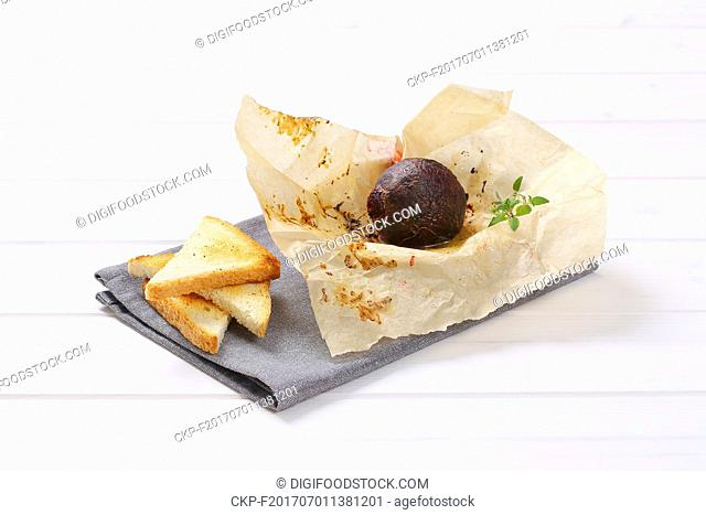baked whole beet with toast on grey place mat