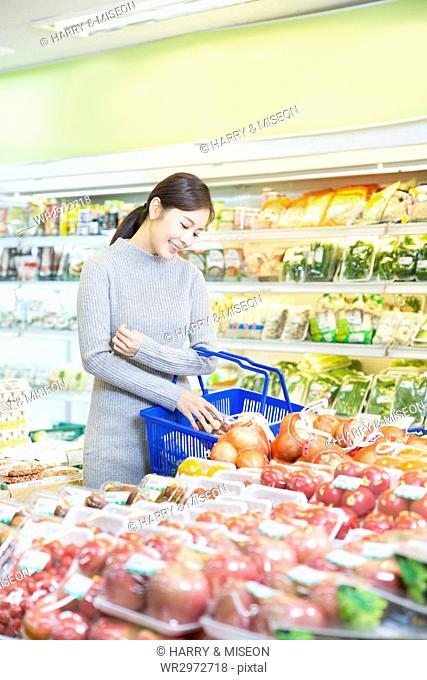 Smiling woman shopping at supermarket