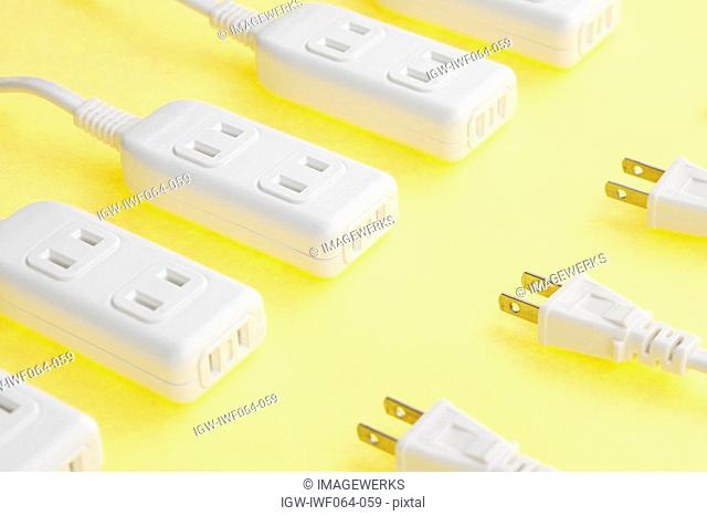 Extension cords and extension sockets on yellow background, close-up
