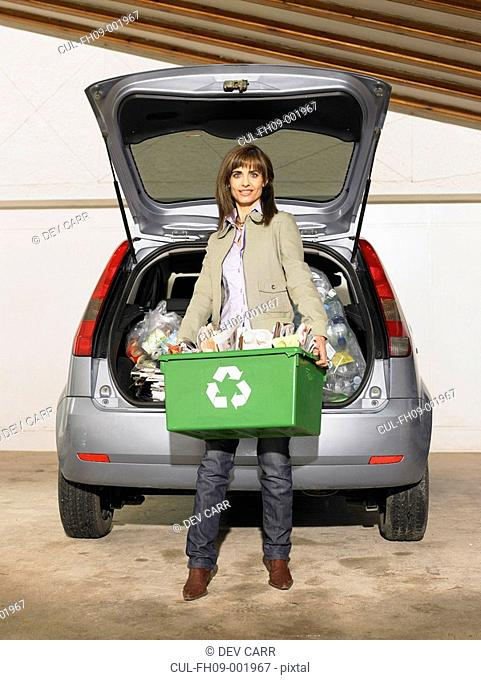 Woman standing of car holding box of recycling, portrait, smiling