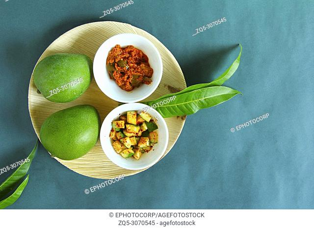 Top view, raw mango, its pieces and mango pickle isolated on green background