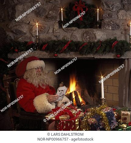 Santa Claus reading a letter by the fireplace