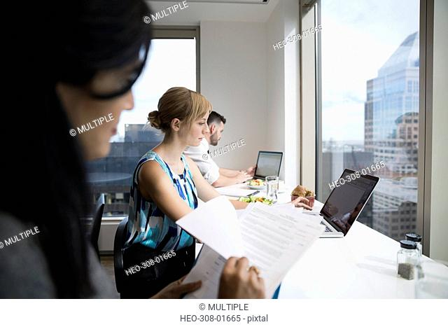 Business people working at laptops and eating lunch in urban office cafeteria
