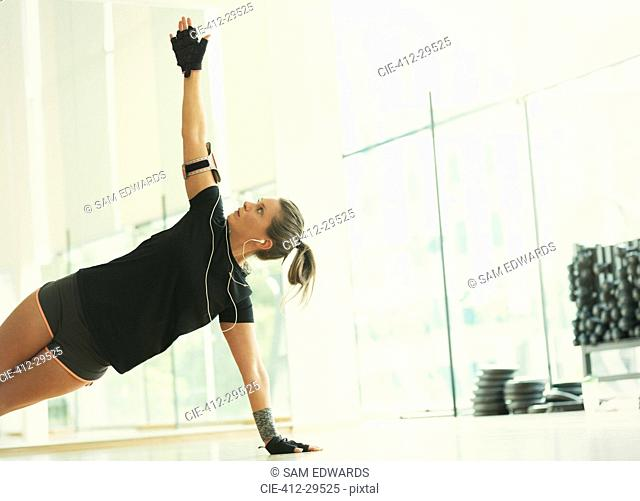 Woman balancing in side plank in gym studio