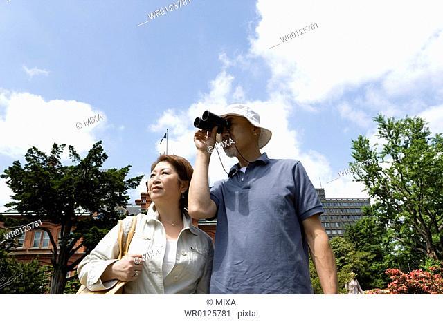 Senior couple standing, man using binoculars