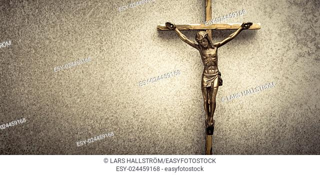 Crucifix of Jesus on the cross with stone background. Symbol of christian religion and belief. Image composed with copy space