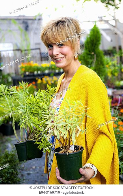 A pretty 42 year old blond woman shopping at a garden store potted euphorbia plants