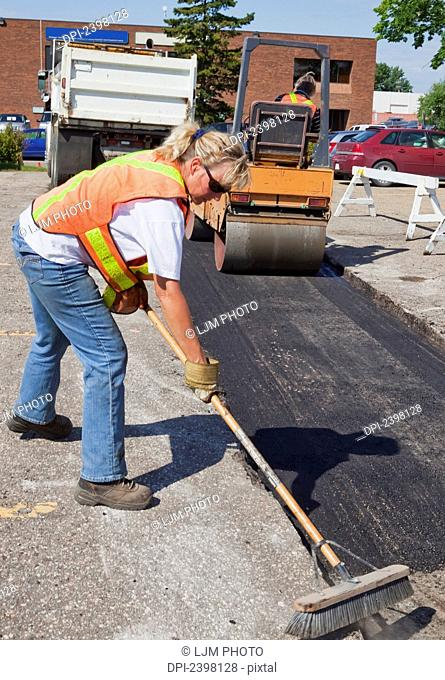 Work crew working to repair pot holes in parking lot; Edmonton, Alberta, Canada