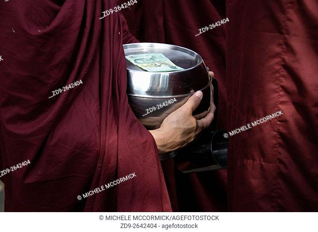 A monk holds his bowl as he stands in line for alms collection
